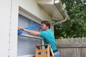 Man taping glass window